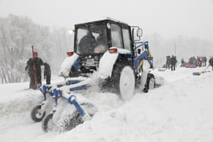 Snow removal as people gather with sledges