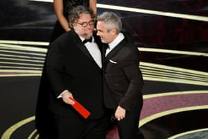 Alfonso Cuarón accepts the best director award for Roma from Guillermo del Toro.