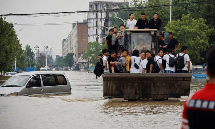 People ride a front loader as they make their way through a flooded road following heavy rainfall in Zhengzhou, Henan province