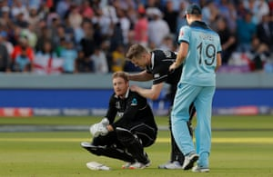 Martin Guptill is consoled by teammate Jimmy Neesham and England player Chris Woakes.