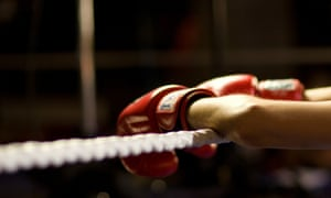 A pair of arms, red boxing gloves on the hands, hanging over the rope of a boxing ring