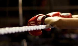 Boxer's gloved hands on a rope