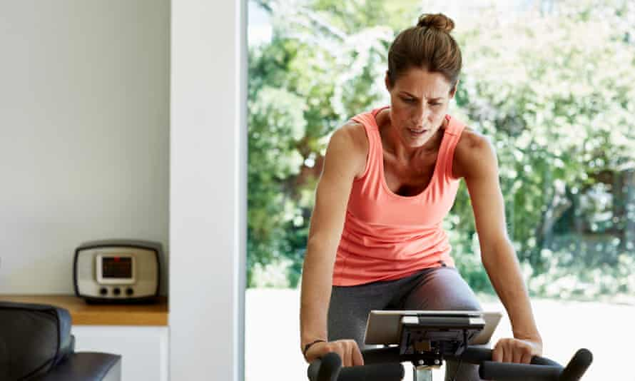 woman on exercise bike in airy living space