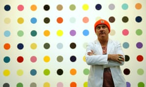 Damien Hirst  in front of one of his dot paintings.