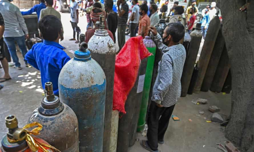 People wait to refill their oxygen cylinders in Delhi.