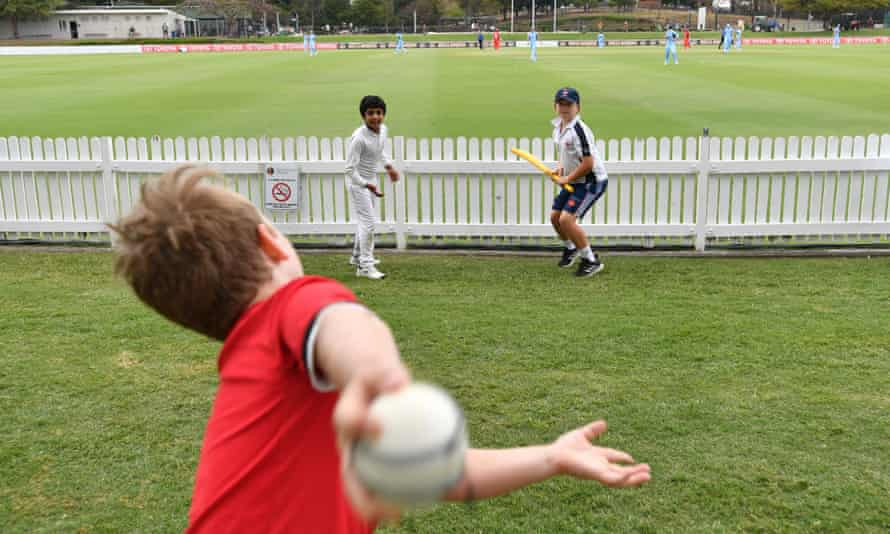 Children play cricket during a break in play at a state cricket match