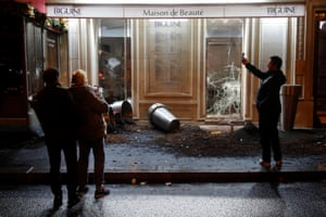 People take pictures of a damaged shop
