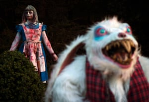A costumed performer dressed as Alice in Wonderland poses with the White Rabbit during the Halloween Horror Party in Bottrop, Germany