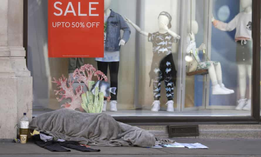 A homeless person sleeps in front of a closed clothing shop in London