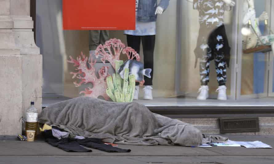 A homeless person sleeps in front of a closed clothing shop in London.