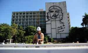A worker paints fixtures for the papal mass in Revolution Square in front of a depiction of revolutionary hero Ernesto 'Che' Guevara.