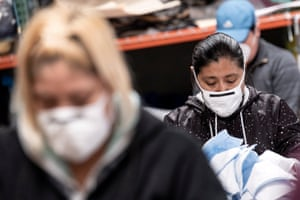 Workers at a sewing shop in Los Angeles wear masks as they make masks for local hospitals.