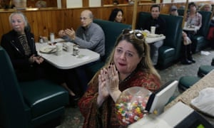 A Hillary Clinton supporter applauds her televised concession speech.