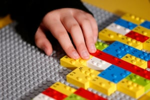 Close-up of a child's hand placing Lego bricks on a board