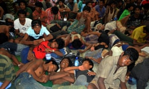 Boat people from Burma and Bangladesh collapsed in exhaustion at the Langkawi police station's multi purpose hall in Langkawi on Monday.