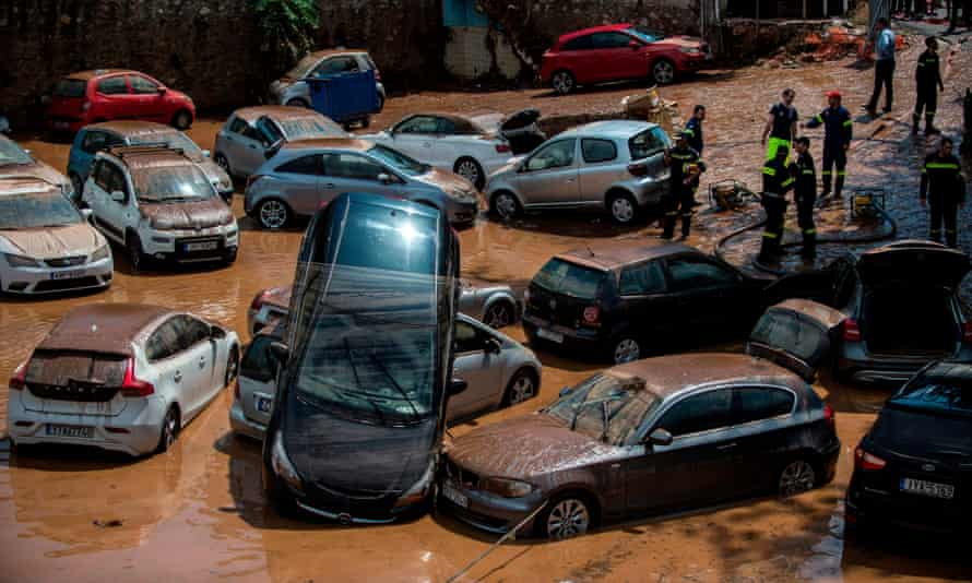 Emergency workers among damaged vehicles in a open parking area of northern Athens after a flash flood struck the Greek capital.