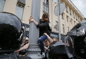 A protester is pulled down from a lamp post during a demonstration in Moscow