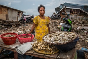 Johariah in front of her makeshift store selling salted fish near the remnants of what used to be her home.