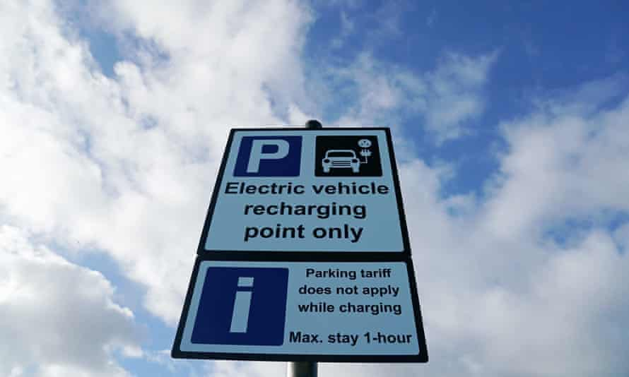 A sign at an electric vehicle charging point at Tynemouth, with a cloudy blue sky above