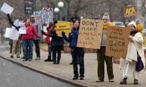 Demonstrators hold signs in the snow