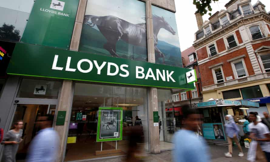 People walk past a branch of Lloyds Bank on Oxford Street in London