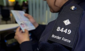A Border Force officer checking a passport.