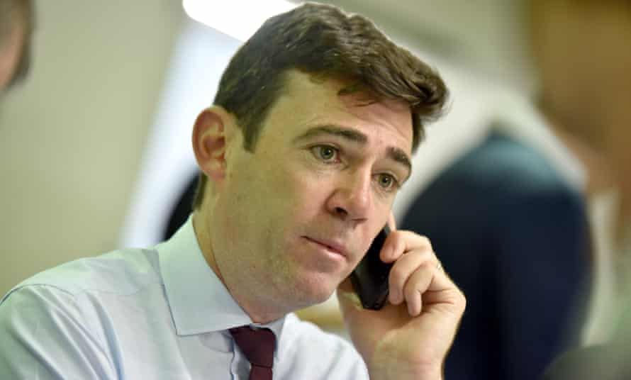 Andy Burnham in shirt and tie holds a cordless phone to his ear