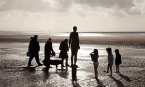 A family with children around one of the Antony Gormley statues ( Another Place ) Crosby Beach, Liverpool, Merseyside, UK