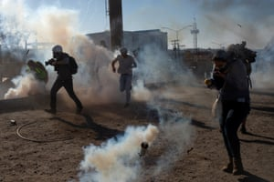 Migrants from Central America and journalists are hit by tear gas after hundreds tried to illegally cross the Mexico border into the US.
