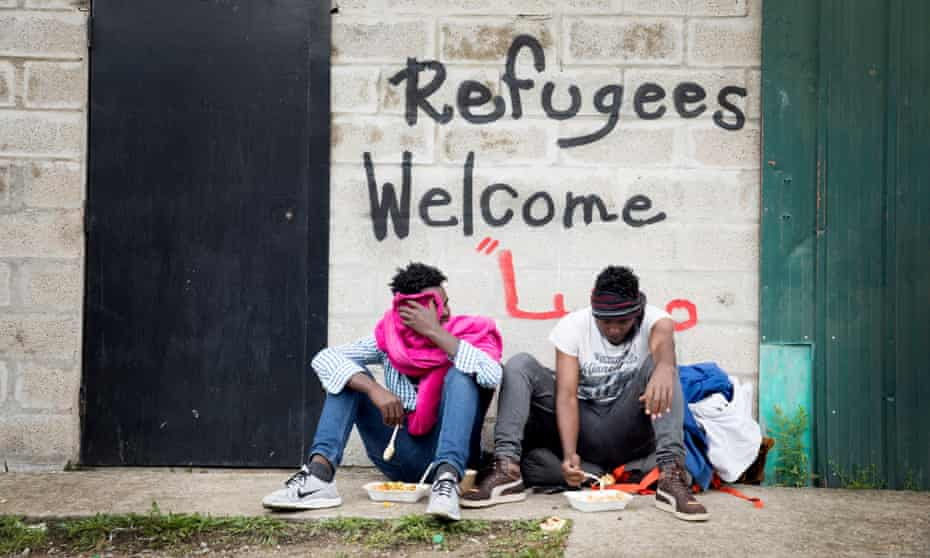 Graffiti sit beneath a sign saying 'Refugees Welcome' in Calais, France.