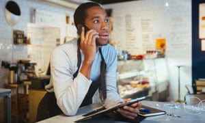 Confident young male employee talking through smart phone while leaning at delicatessen