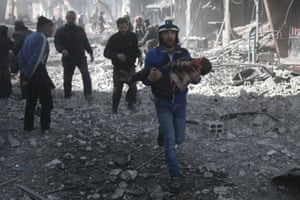 A member of the White Helmets carries an injured child rescued from between the rubble of buildings
