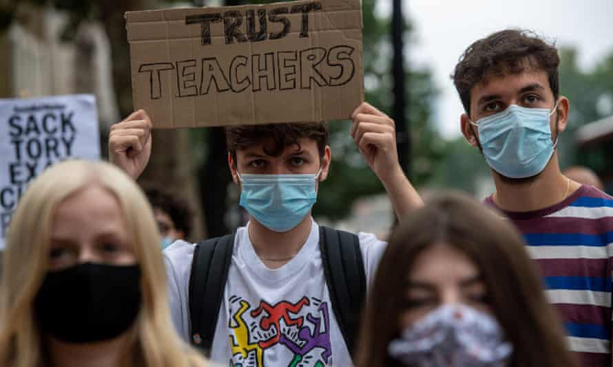 Students, teachers and parents hold placards and wear face masks as they protest against downgraded A level results in London yesterday