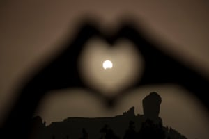 A woman makes a heart shape with her hands during a partial eclipse of the sun