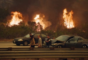 A woman involved in a traffic accident waits to get towed beside a wall of flames on the 101 highway near Ventura