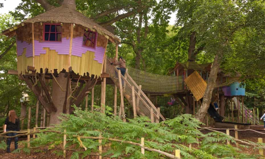 Amid the trees, during a grey day, an image of a treehouse at Bewilderwood, Norfolk