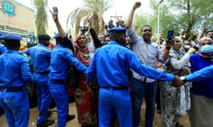 Sudanese police officers control civilians as they chant slogans outside court on Tuesday.