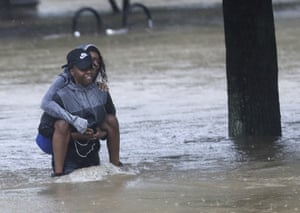 Houston residents wade through floodwater.