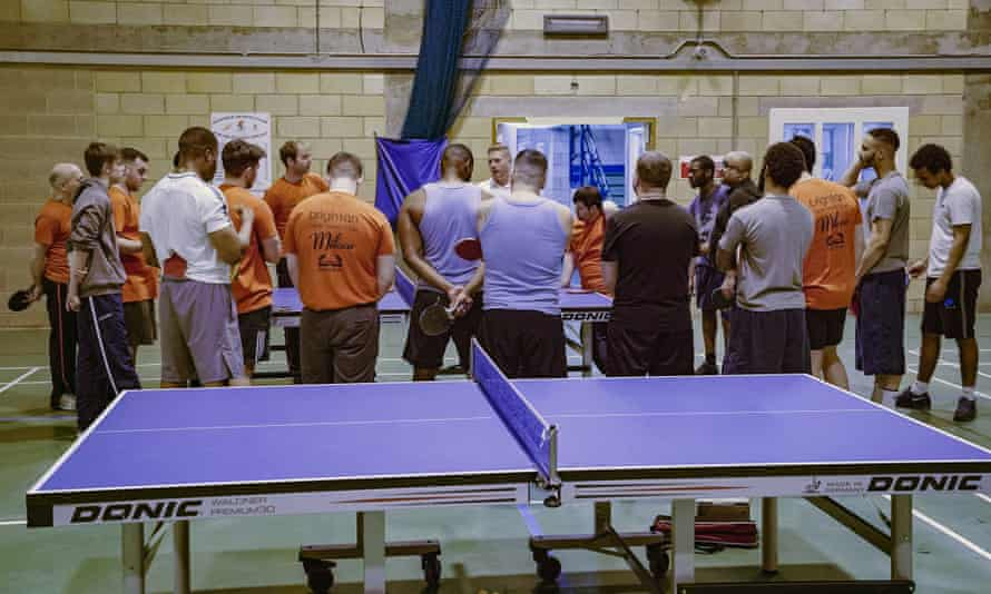 High Down prisoners and volunteers from Brighton Table Tennis Club gather in the prison gym after a session.