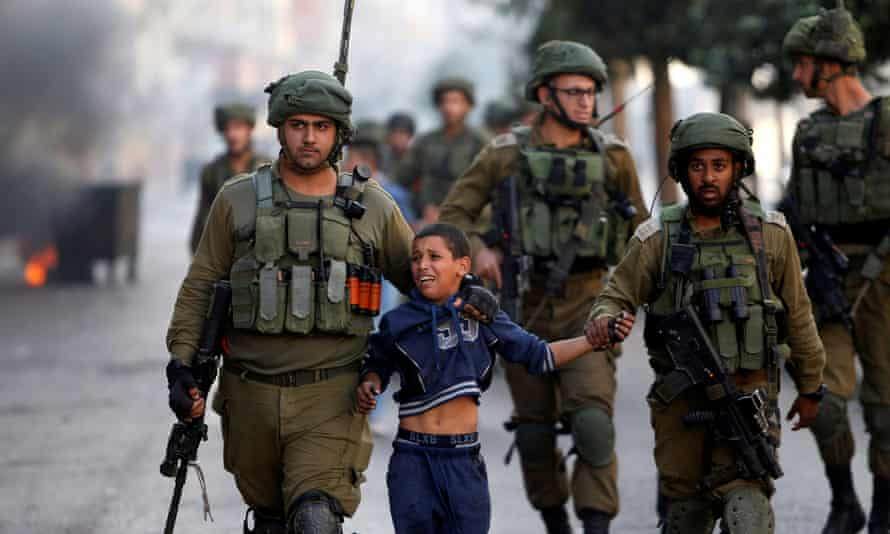 Israeli soldiers detain a Palestinian boy during clashes in the West Bank city of Hebron
