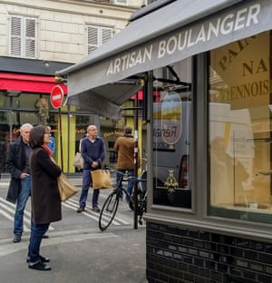 Customers queue at the Condorcet bakery, keeping a safe distance from each other