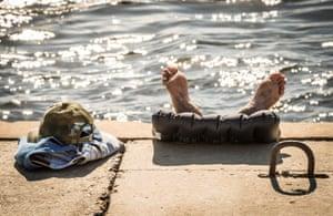 A man sunbathes on the bank of the Volga river, Volgograd, Russia
