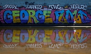 A child walks by a mural at the Cal Anderson Park Reflecting Pool as protesters against racial inequality occupy space at 'Chop' in Seattle, Washington.