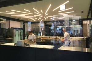 Brother and sister Kate and Cameron Reid preparing croissant pastry in a temperature-controlled glass cube in the middle of their store.