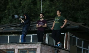 Iranian female photographer Parisa Pourtaherian who covered a recent football match from a nearby rooftop.