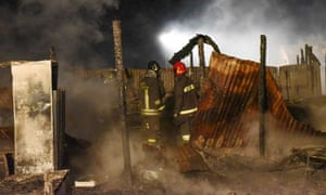 Firefighters extinguish flames at a refugee camp in Rignano Garganico, Italy.