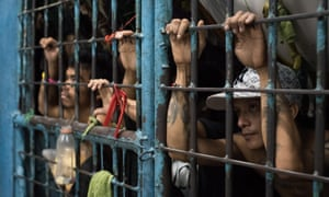 Inmates look outside from an overcrowded police jail cell in Manila, Philippines.