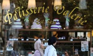 Women walk past a branch of Patisserie Valerie in London.