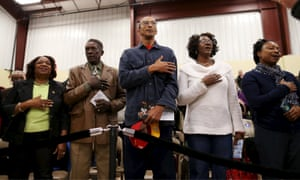 People sing the national anthem before a speech by Democratic presidential candidate Hillary Clinton at the Williamsburg County Recreation Center in Kingstree, South Carolina on Thursday.