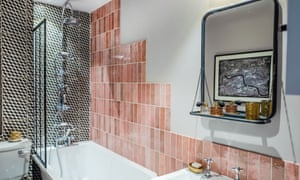 The bathroom with a shower over the bath, black and white tiles behind, and stepped pink tiles on the long wall